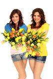 Young women with flowers. Young brunette women with yellow and red flower Bouquet stock photography
