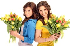 Young women with flowers. Young brunette women with yellow and red flower Bouquet royalty free stock photos