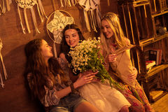 Young women with flowers. Beautiful smiling young women sitting on bench with bouquets of flowers Royalty Free Stock Images