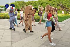 Young women followed by two persons dressed like animals. Event: Football and Music Festival Art-football. Date: May 27, 2016. Location: Gorky recreation park Royalty Free Stock Photos