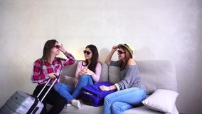 Cute girls going on trip  preparing suitcases couch in afternoon room. Young women fool around and laugh, measure glasses and posing on camera in good mood stock video
