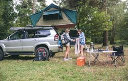 Young women in campsite packing blanket for hiking. Young women friends in campsite packing blanket for a hiking trip into the forest Royalty Free Stock Photos