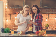 Young women friends cooking meal together at home Royalty Free Stock Photos
