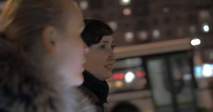Women having friendly talk during evening walk in the city. Young women friends having a talk while walking in the street of evening city stock footage