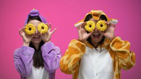 Young women in funny pajamas closing eyes with donuts, fooling around, joke. Stock footage stock video footage