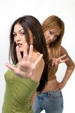 Young women gesturing. Two young, diverse girls making hand gestures: stop and peace signs Stock Image