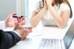 Young woman getting fired from work in office. Young women getting fired from work in office. Boss complaining or giving negative feedback to unhappy worker royalty free stock photography