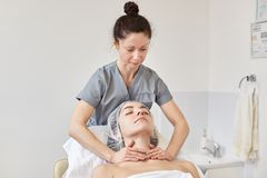 Young woman getting spa massage treatment at cosmetologi clinic. Facial beauty treatment, relaxing in beauty salon, preparing for royalty free stock photography