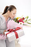 Young women with gift and flowers Royalty Free Stock Photos
