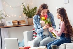 Mother and daughter at home mother`s day sitting mother smelling flowers daughter gift stock photo