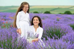 Young woman and girl are in the lavender field, beautiful summer landscape with red poppy flowers Royalty Free Stock Photo