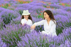 Young woman and girl are in the lavender field, beautiful summer landscape with red poppy flowers Royalty Free Stock Images