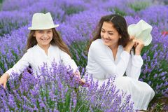 Young woman and girl are in the lavender field, beautiful summer landscape with red poppy flowers Stock Photos
