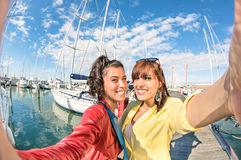 Young women girlfriends taking summer selfie at harbour docks. Young women girlfriends taking a selfie at harbour docks with sailboats - Concept of friendship Royalty Free Stock Photo