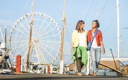Young women girlfriends walking together on public jetty pier. Docks with ferris wheel on background - Best female friends traveling on european summer royalty free stock photography