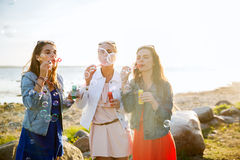 Young women or girls blowing bubbles on beach Royalty Free Stock Images