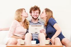 Women girls kissing man guy with tablet. Fun. Young women girls kissing handsome men guy with tablet. Happy friends having fun relaxing at home Royalty Free Stock Photography