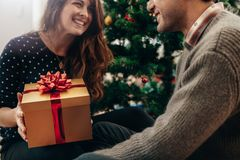 Young couple celebrating Christmas by exchanging gifts. Stock Photography
