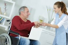 Young woman giving glass water to disabled man Royalty Free Stock Photos