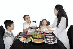 Young woman giving meals to her family Stock Photography
