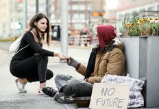 Young woman giving money to homeless beggar man sitting in city. royalty free stock photo