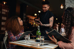Young women giving order to a waiter at cafe. Portrait of a young women giving an order to a waiter at a cafe sitting with her friend. Waiter putting order onto Royalty Free Stock Photo