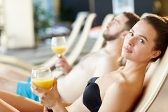 Restful girl. Young women with glass of orange juice enjoying her vacation at spa resort Royalty Free Stock Photos