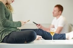 Woman checking her smartphone. Young women with glass of wine checking social media on her smartpone when husband watching tv at home stock images