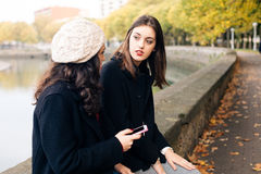 Young women gossiping outdoors Stock Photo