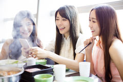Young Women group  Eating hot pot. And taking picure by phone Stock Images