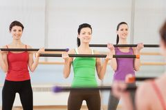 Young women in gym doing exercises with fitness sticks. Royalty Free Stock Photography