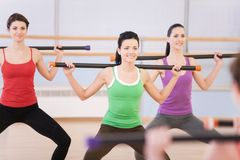 Young women in gym doing exercises with fitness sticks. Royalty Free Stock Image