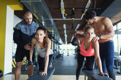 Young women in gym doing exercises with trainers. Young women in gym doing exercises with their trainers stock photography