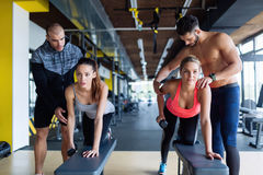 Young women in gym doing exercises with trainers. Young women in gym doing exercises with their trainers royalty free stock photo