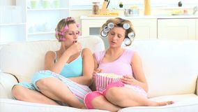 Young women with hair rollers eating popcorn on the sofa. In the living room stock video footage