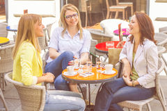 Young Women have Coffee Break Together. Three Young Women have Coffee Break Together in street cafe. Caucasian female relaxing on beautiful summer day in the Stock Photography