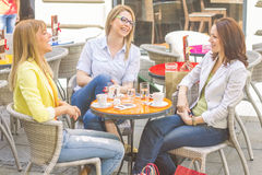 Young Women have Coffee Break Together. Three Young Women have Coffee Break Together in street cafe. Caucasian female relaxing on beautiful summer day in the Stock Image