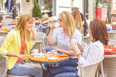 Young Women have Coffee Break Together. Three Young Women have Coffee Break Together in street cafe. Caucasian female relaxing on beautiful summer day in the Royalty Free Stock Photography