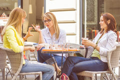 Young Women have Coffee Break Together. Three Young Women have Coffee Break Together in street cafe. Caucasian female relaxing on beautiful summer day in the Royalty Free Stock Photo