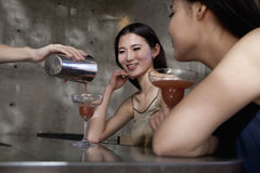 Young women having cocktails, sitting at the bar counter Stock Photos