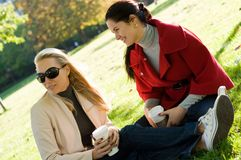Young women having coffee break together in park Stock Photos