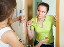 Young women having conflict at the door. Two displeased young female neighbours having conflict at the door Royalty Free Stock Image