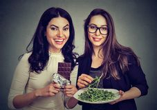 Young women having different diets. Young models experiencing opposite dieting posing with plate of rucola and bar of chocolate stock image