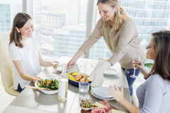 Young women having dinner together in modern kitchen Stock Images