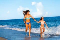Young women having fun along beach. Stock Photography