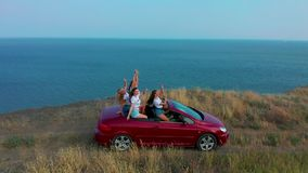 Aerial view. Young women having fun in convertible on the seaside. stock video