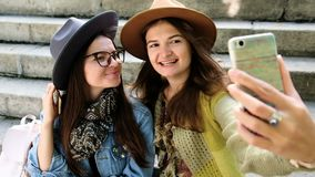 Young women having fun and taking selfies close up. Young woman friends having fun and taking selfies sitting on the stairs stock video
