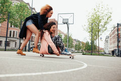 Young women having fun together with skateboard Royalty Free Stock Photo