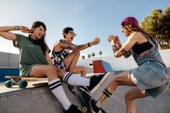Young women having a great time at skate park. Three young women having a great time at skate park. Young female skateboarding with friends sitting on ramp Stock Photography
