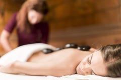 Spa hot stone massage. Young women having a hot stone massage stock image